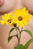 Yellow flower against a female body — Foto Stock