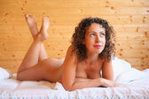 Naked beautiful hot woman lying on bed in cosy wooden room — Stock Photo