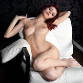 Naked woman on the armchair — Stockfoto