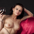 Nude woman on a satin bedenjoying a glass of red wine — Stock Photo