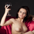 Nude woman on a satin bed enjoying a glass of red wine — Stock Photo