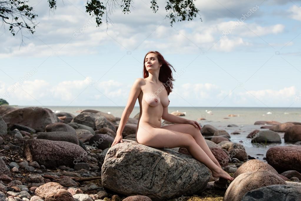 Nude Woman Sitting On Stone Stock Image