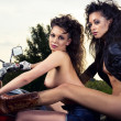 Two sexy young woman sitting on a motorcycle outdoors — Stock Photo