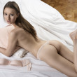 Sexy nude girl lying on the white bed with pillow in her arms — Stock Photo #12425189