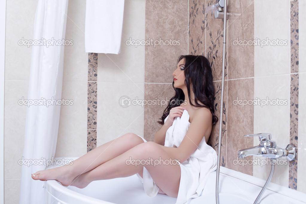 Молоденькая брюнетка позирует в ванной  593410