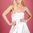 Cute blond in white dress on pink background — Stock Photo