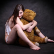 Young homeless girl is holding the teddy bear. Conceptual image - recession metaphor. — Stock Photo