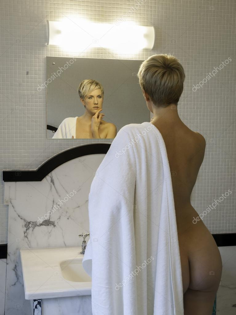 Woman With The Towel Looking In The Bathroom Mirrow
