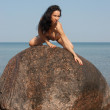 Young nude woman kneeling on a rock against the sea - Stock Photo