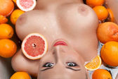 Woman with big breast relaxing in the bath with oranges — Stock Photo