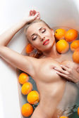 Woman  showing bare breast in the bath with oranges — Stock Photo